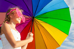 Teen girl standing with umbrella on the blue sky background Stock Photo