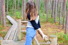 Teen girl standing on wooden pathway stock images