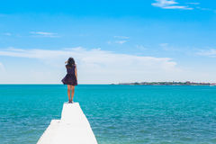 A teen girl stands on the background turquoise sea. A teen girl stands on a white pier on the background turquoise sea, her hair and dress fluttering in the wind Royalty Free Stock Photography