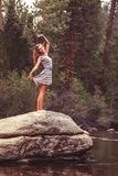 Teen girl stands on large rock stretching arms Stock Image