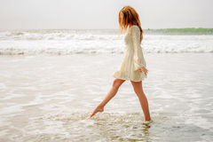 Teen girl stepping in the waves Stock Photo