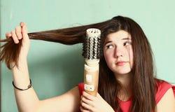 Teen girl straighten her long brown hair Royalty Free Stock Photo
