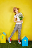 Teen girl in straw hat holding spring flowers. Stock Photography