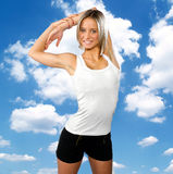 Teen girl stretching her arms. In front of sky background Stock Image