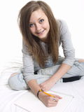 Teen girl studying. A teenage girl sitting on the floor or bed, writing in a notebook as she studies Royalty Free Stock Images