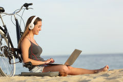Teen girl studying with a laptop on the beach. Leaning on a bicycle Royalty Free Stock Photos