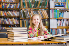 Teen girl studying at library Royalty Free Stock Images