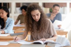 Teen girl studying with textbook writing essay learning in classroom stock images