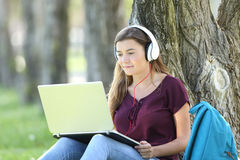 Teen girl studying watching video tutorials Royalty Free Stock Photo