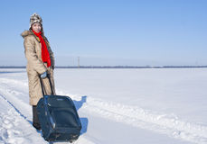 Teen girl with a suitcase. Outdoors at winter time Stock Photography
