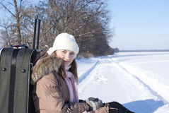 Teen girl with a suitcase outdoors. At winter time Stock Photography