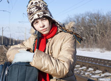 Teen girl with a suitcase outdoors. Teen girl with a suitcase near the railways at winter time Stock Photos
