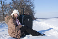 Teen girl with a suitcase outdoors. At winter time Royalty Free Stock Image
