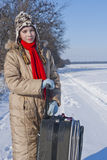 Teen girl with a suitcase outdoors. At winter time Stock Photos
