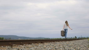 Teen girl with suitcase walking on the railway at the day time. Concept of happiness stock video