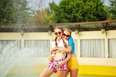 Teen girl in sunglasses hugging. Teen girl in sunglasses hugging near the fountain in summer park. Girls dressed in shorts and a shirt. On summer vacation. The Stock Image