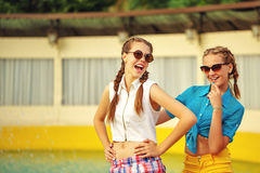 Teen girl in sunglasses laugh. Teen girl in sunglasses laugh near the fountain in summer park. Girls dressed in shorts and a shirt. On summer vacation. The Stock Photo