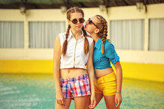 Teen girl in sunglasses. Teen girl in sunglasses standing near the fountain in summer park. Girls dressed in shorts and a shirt. On summer vacation. The concept Royalty Free Stock Image