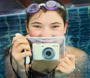 Teen girl in swimming pool with underwter camera Royalty Free Stock Photography