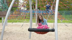 Teen girl on swing. Happy teen girl with tablet pc and backpack on swing in playground outdoors. Beautiful student teenager using gadget. Child having fun after stock video footage