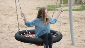Teen girl on swing. Happy teen girl on swing in playground outdoors. Beautiful student teenager swinging on swing in summer park. Child having fun after school stock footage