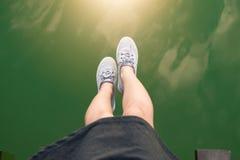 Teen girl swing legs wear sneaker on green river. Stock Photo