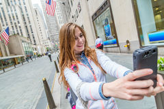Teen girl taking selfie in the street. A cute smiling young woman takes a picture of herself while standing outside on a street against a background of high rise Royalty Free Stock Photo