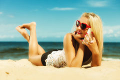 Teen girl talking on mobile phone on beach. Technology and communication. Young woman teen girl talking on mobile cell phone using smartphone on beach Royalty Free Stock Images