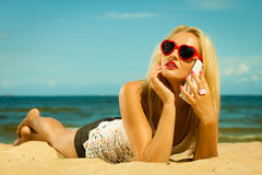 Teen girl talking on mobile phone on beach. Technology and communication. Young woman teen girl talking on mobile cell phone using smartphone on beach Royalty Free Stock Image
