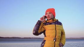 Teen girl talking on phone on background of bay. stock video