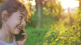 Teen girl talking on the phone behind the sunset golden hour nature forest outdoors slow motion video. Teen girl talking on the phone behind sunset golden hour stock video