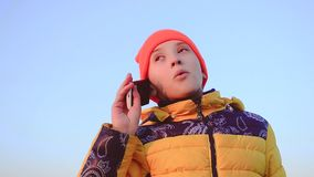 Teen girl talking on phone on blue the sky background. stock footage