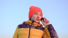 Teen girl talking on the phone on blue sky background. stock video