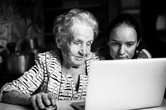 Teen girl teaches her grandmother to type on the laptop. Help. Royalty Free Stock Photo