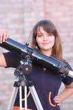 Teen girl and telescope stock image