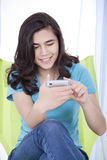 Teen girl texting on a cell phone. Biracial teen girl or young woman texting on cell phone, smiling Stock Photography