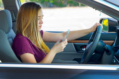 Teen girl texting and driving. Teen girl texting while driving Stock Photo