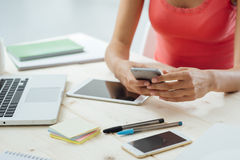 Teen girl texting with her mobile phone. Teen girl sitting at desk and texting with her mobile touch screen phone, hands close up, unrecognizable person Stock Photo