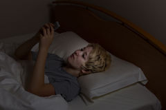 Teen girl texting late at night while in bed. Teenage girl using her cell phone while in bed. Teen using technology late at night instead of sleeping Royalty Free Stock Image