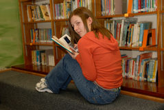 Teen Girl Texting in Library. A teenager sneaks a text message on cell phone during school library Royalty Free Stock Images