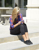Teen girl texting on a mobile phone. Teenage girl sitting on concrete steps while texting on a mobile phone and hold cup of coffee in the other hand Royalty Free Stock Images