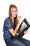 Teen girl thinking. A teenager schoolgirl, with her pen in her mouth, thinking about her homework, in jeans and a chickened blue blouse, over white royalty free stock photos