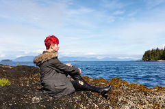 Teen girl thinking while sitting on rock near lake and woods Stock Photos