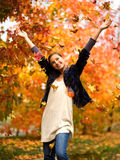 Teen girl throwing leaves in autumn Stock Photography