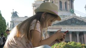 Teen girl tourist sitting searching information on a smart phone on vacations on the city street. Technology, leisure stock footage