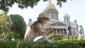 Teen girl tourist sitting searching information on a smart phone on vacations on the city street. Technology, leisure stock video