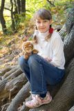Teen girl with toy tiger. Grass in an autumn park Royalty Free Stock Image