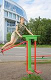 Teen girl trains on a swinging simulator outdoors Royalty Free Stock Images