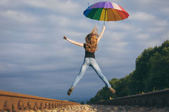 Teen girl with umbrella jumping on the railway at the day time. Stock Photo