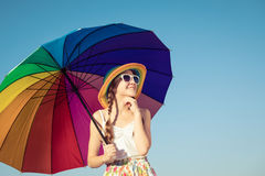 Teen girl with umbrella standing on the beach at the day time. Kid having fun on the nature. Concept of happiness Royalty Free Stock Image